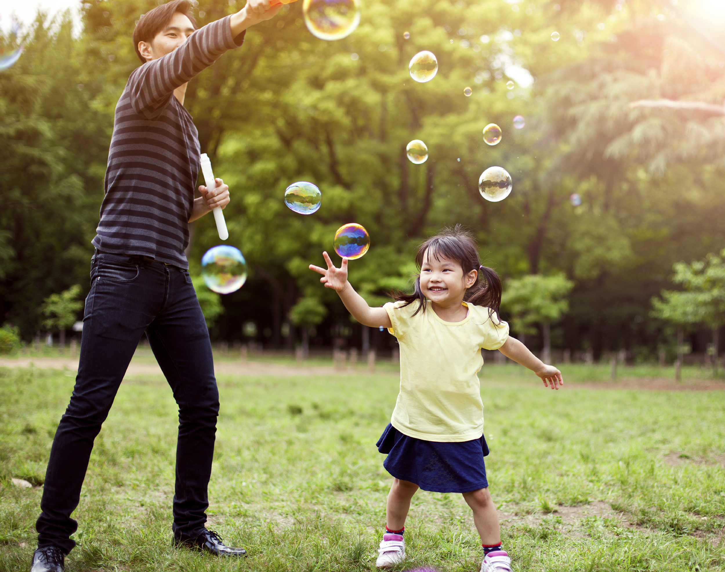 Man playing with bubble with little girl