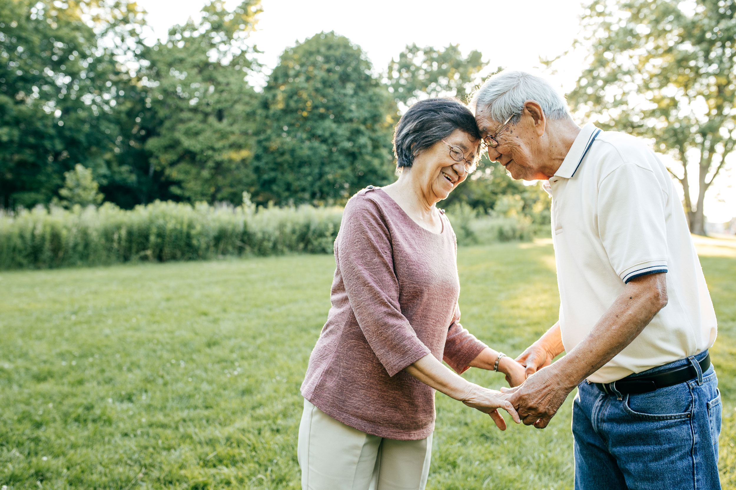 Photo of a couple in their 60s or 70s holding hands while pressing their foreheads against one another and smiling.