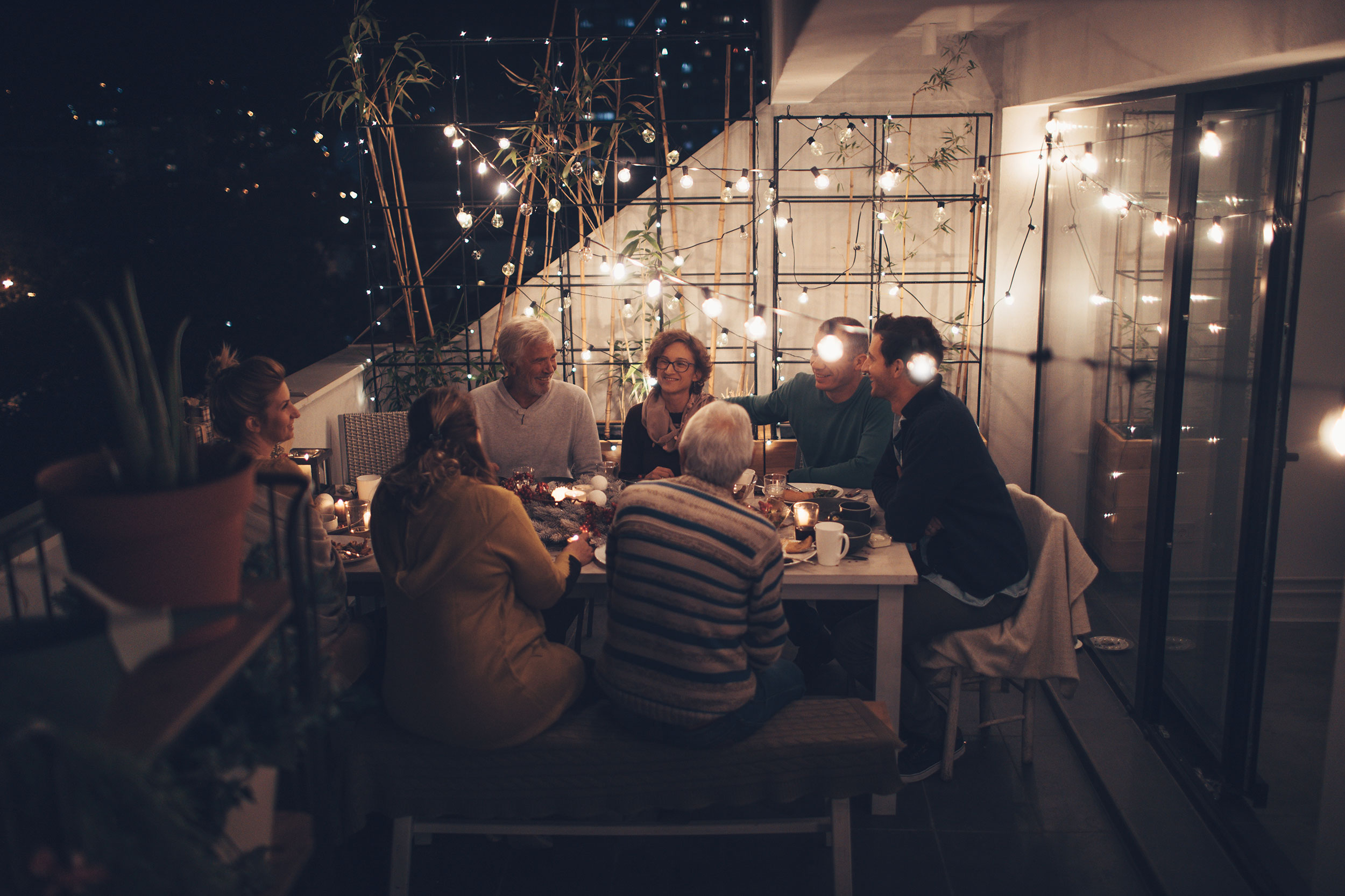 Photo of a family around the dinner table for Passover, shown laughing and enjoying each other's company.